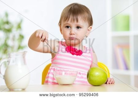 happy child girl eating food itself with spoon