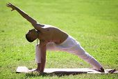 picture of extend  - Profile of handsome sporty Indian young man exercising in park in summer doing yoga fitness or pilates training standing in lunge exercise Utthita Parsva Konasana  - JPG