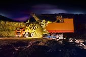 image of open-pit mine  - A picture of a big yellow mining truck at worksite  - JPG