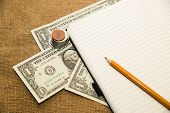 pic of memento  - Opened notebook with a blank sheet pencil and money on the old tissue - JPG
