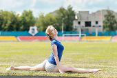 foto of do splits  - Pretty woman doing exercises at a stadium - JPG