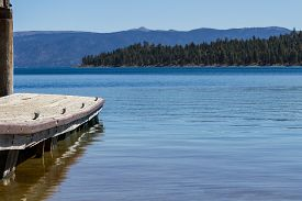 pic of dock a lake  - view of a dock in Lake Tahoe with no boats on the lake a peaceful and relaxing landscape - JPG