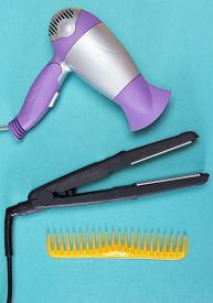 picture of hair comb  - Hair styling iron hairdryer and wide tooth comb on blue background - JPG