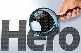 picture of opposites  - Human hand holding magnifying glass reading the word HERO hiding the opposite message VILLAIN - JPG