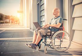 picture of handicapped  - Disabled man on the wheelchair working with laptop computer outdoors  - JPG