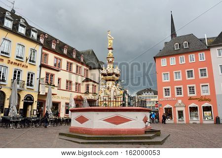 Trier, Germany - April 26, 2016. View of Hauptmarkt square in Trier, with historic fountain dating from 1595, historic buildings, commercial properties and people.