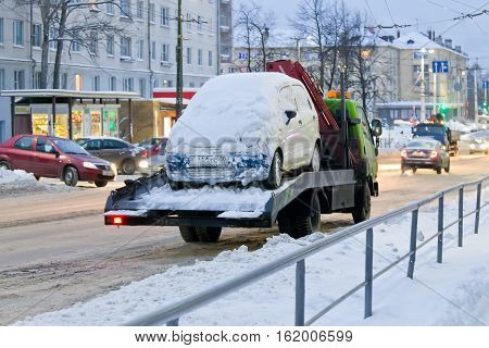 PETROZAVODSK, RUSSIA - DECEMBER 16TH, 2016: Tow truck taking away the car, which hinders the cleaning of streets from snow