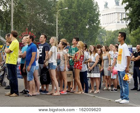 MOSCOW, RUSSIA - July 24, 2016: People standing in a queue for park amusement watching attraction in the Park of VDNH. July 24, 2016 in Moscow, Russia
