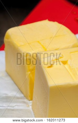 Two blocks of unwrapped butter, thawing to soften in preparation for consumption.