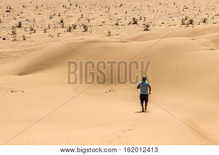 Man tourist in desert rub al khali in Oman running in sand