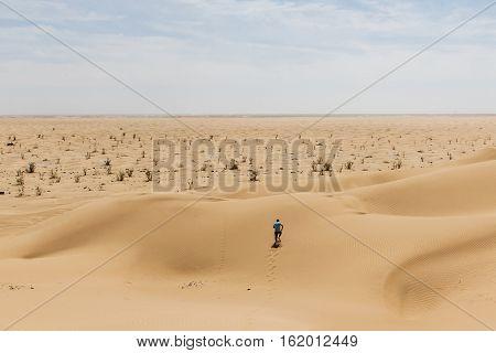 Man tourist in desert rub al khali in Oman running in sand 2
