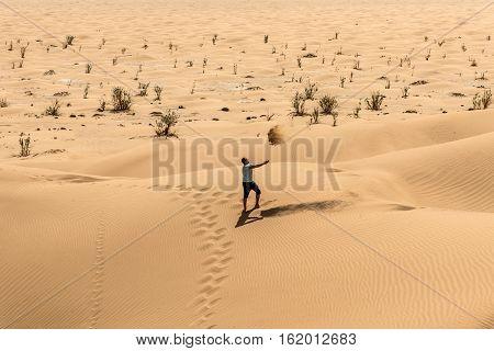 Man tourist in desert rub al khali in Oman throwing sand 2