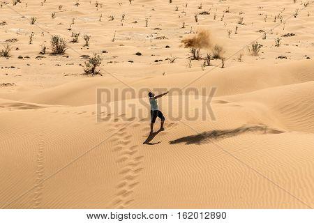 Man tourist in desert rub al khali in Oman throwing sand 4