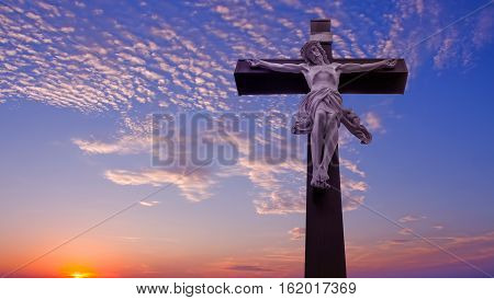 Christian cross with Jesus Christ over sunset panoramic view
