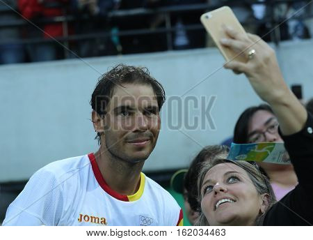 RIO DE JANEIRO, BRAZIL - AUGUST 12, 2016: Olympic champion Rafael Nadal of Spain taking selfie with tennis fan after men's singles semifinal of the Rio 2016 Olympic Games at the Olympic Tennis Centre