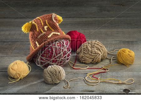 balls of yarn and knit cap on a wooden table