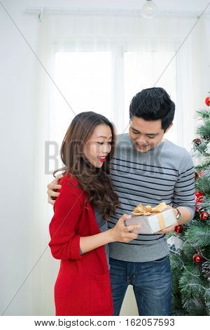 Christmas Asian Couple. A Handsome Man Giving Her Girlfriend/wife A Gift At Home Celebrating New Yea