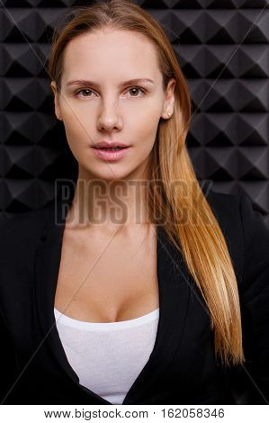 Woman in black cardigan on empty black background