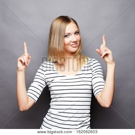 Portrait of cheerful young woman showing copyspace, visual imaginary or something, or pressing virual button,  over grey  background