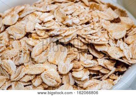Heap of rolled oats in a cup or scoop. High-resolution closeup view.