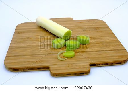 Fresh Leeks Whole And Sliced On A Wooden Kitchen Board.