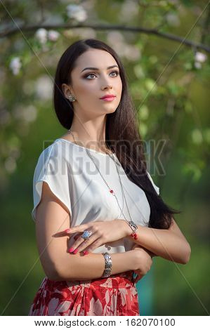 Beautiful yong model wearing luxury accessory in blooming spring garden