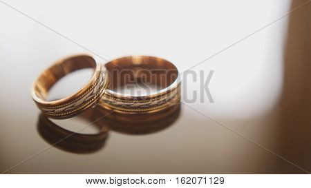 Golden wedding rings on mirror glasses table - one lies on top of another, horizontal, close up
