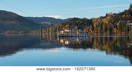 Pleasure boat with tourists on Titisee in the sunny autumn day, Germany