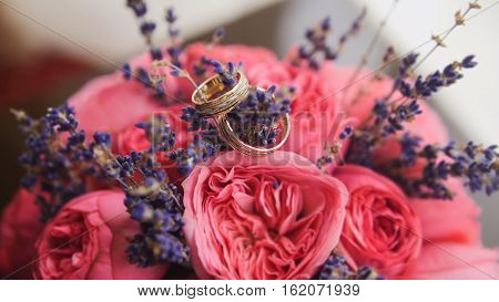 Golden wedding rings in center of bride's bouquet, close up