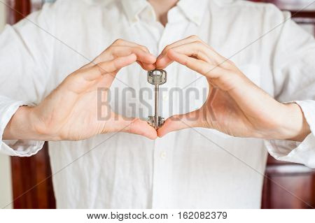 Men's Hands Hold House Key In The Form Of Heart On The Background Of A Wooden Door. Owning Real Esta