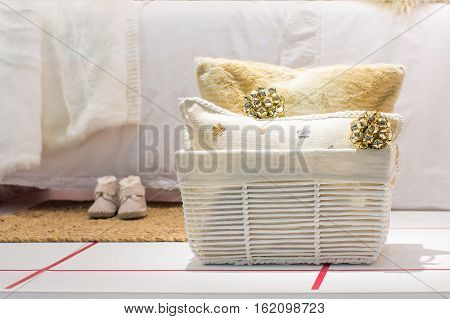 Christmas composition of basket with two pillows and christmas toys near a bed