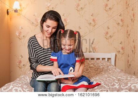 Mother teach to read her little daughter.