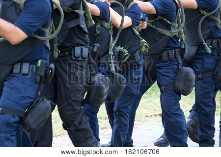 tactical movement of law enforcement in blue uniform training with tactical equipment in academy