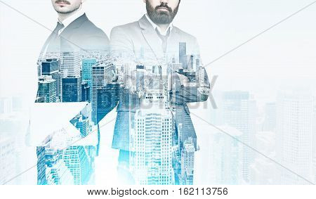 Portrait of two businessmen. One is standing with his arms crossed the second is holding a laptop. Cityscape is at the foreground. Film effect. Toned image. Mock up. Double exposure
