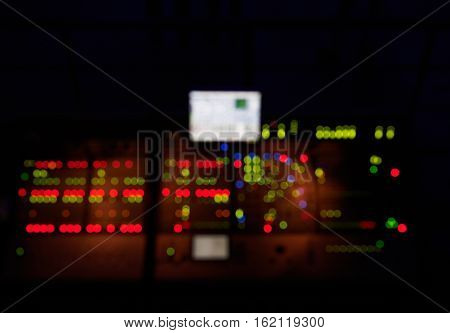Blurred sound work place with red and green lights. Music mixer in night club.