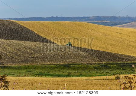 SUMMERTIME: HILLY RURAL LANDSCAPE .Between Apulia and Basilicata; plowing with tractor in agricultural land after the harvest. -ITALY-