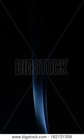 Blue abstract smoke art plume on a black background vertical view