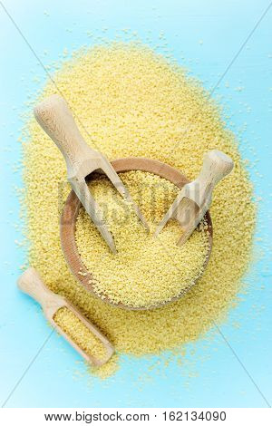 Raw organic couscous on a blue background
