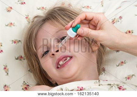 Little girl does not want to her nose dripped with a pipette