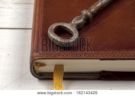 old keys on a old book on rustic wooden background. Copy space for text.
