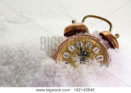 Vintage alarm clock in the snow shows five minutes before twelve concept for new year with copy space