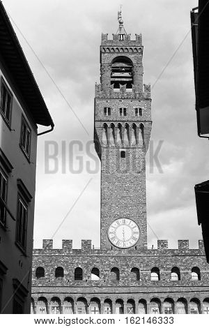 Monochrome image of Clock tower of Palazzo Vecchio building in Florence Italy