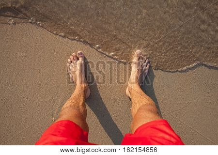 Man's legs in red shorts on the sand beach and sea waves at sunset
