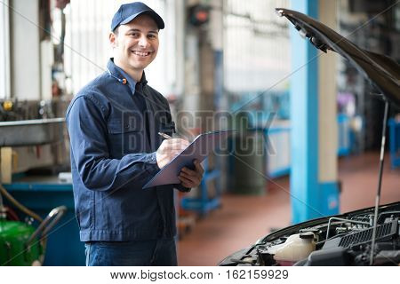 Portrait of a mechanic writing on a clipboard in his garage