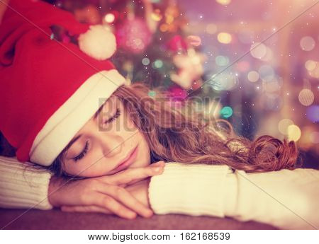 Closeup portrait of a nice girl waiting for a Christmas gifts, tired child wearing red Santa hat sleeping in the decorated room at home, winter holidays concept