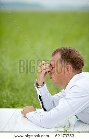 Businessman rubbing his tired eyes outdoors in green field