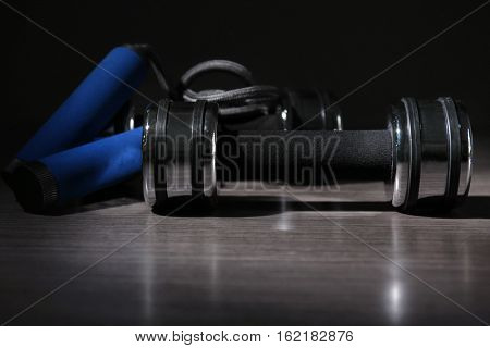 Dumbbell and skipping rope on wooden surface against dark background