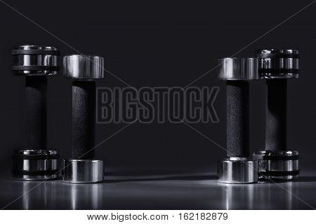Four dumbbells on dark background