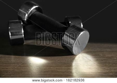 Dumbbells on wooden surface against dark background