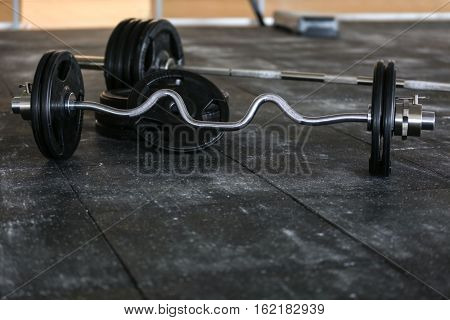 Barbells and weight plates on floor in gym